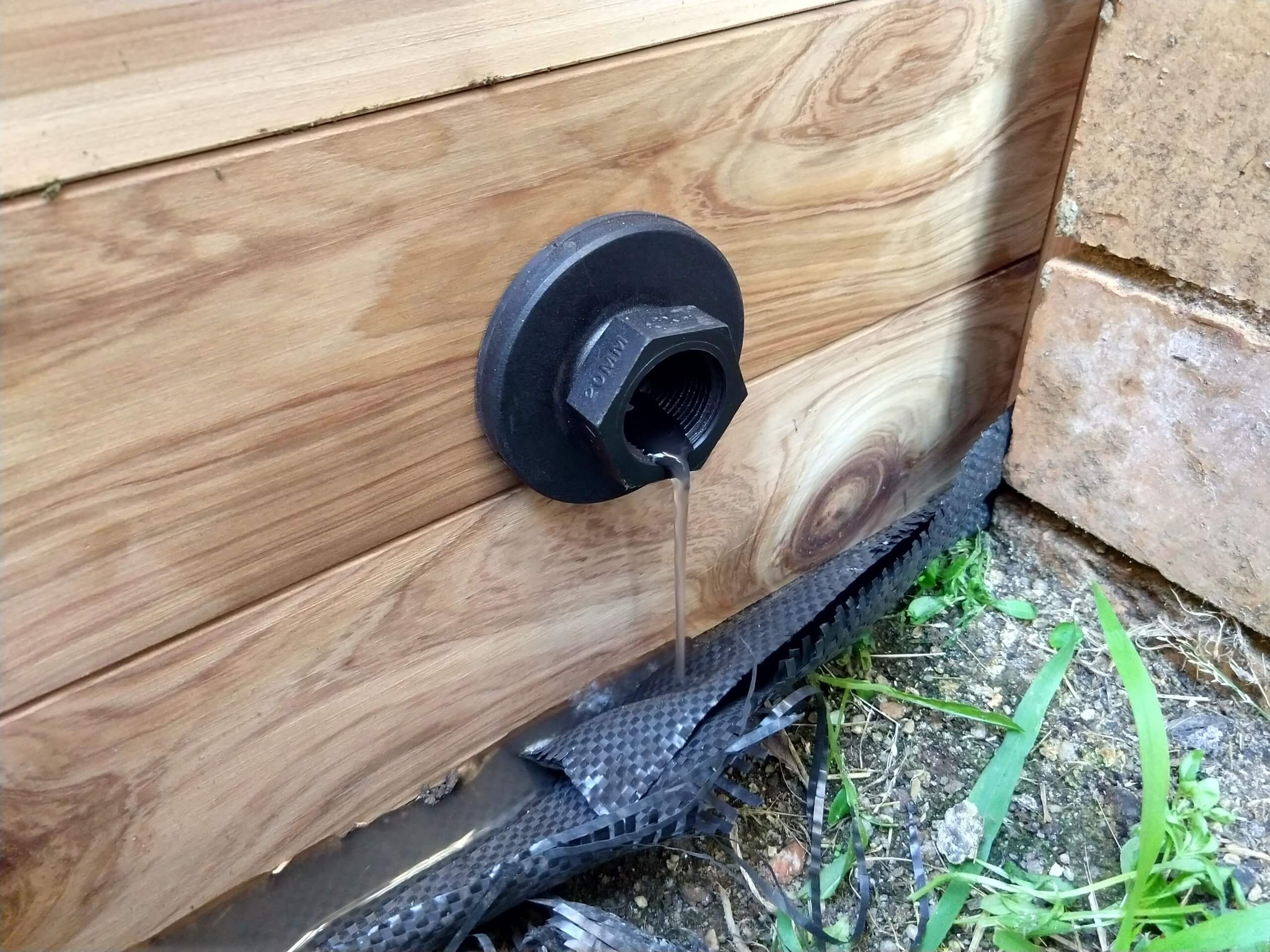 A plastic drain outlet in the side of a wooden garden bed with a small amount of water dripping from it.