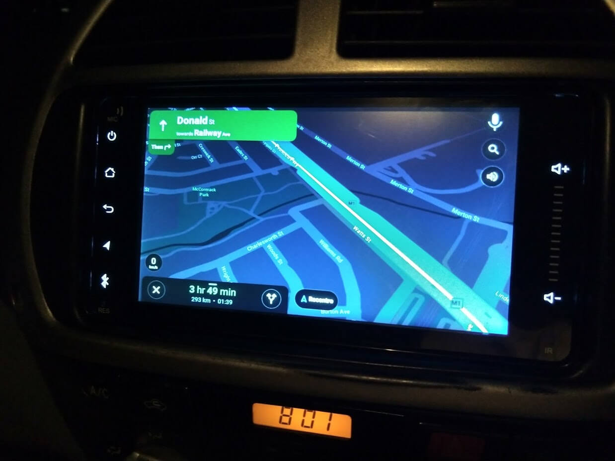 A LCD screen mounted in a car showing an Android Auto maps display